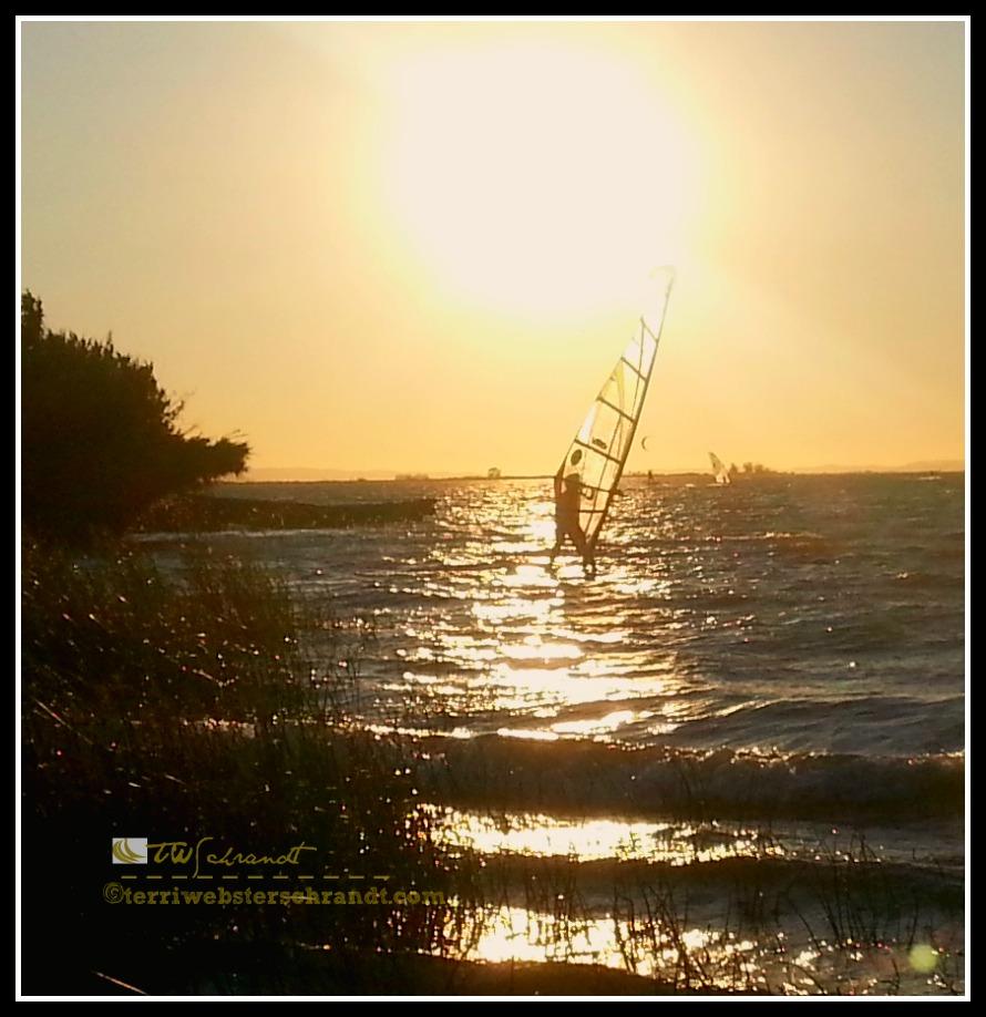Summer Sun sets on windsurfer getting the last bits of wind.