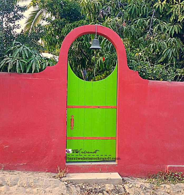 Vibrant gate guards a homey villa in Baja, Mexico.