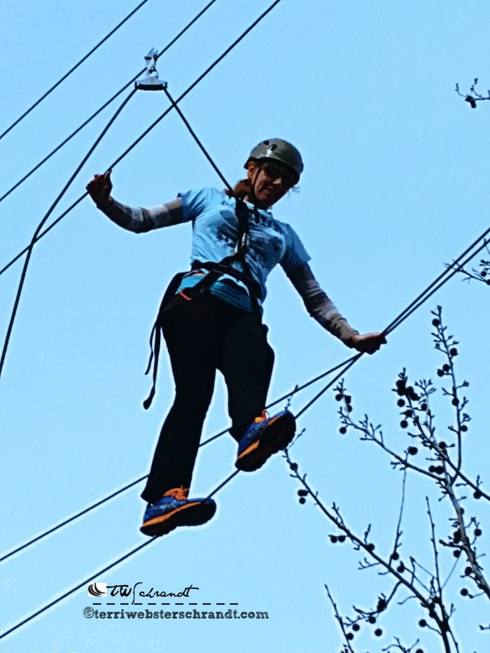 Students close-up of 40-feet high tightrope shows determination and motivation.