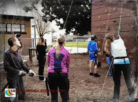 University Students belay rock wall climbers at the Challenge Course