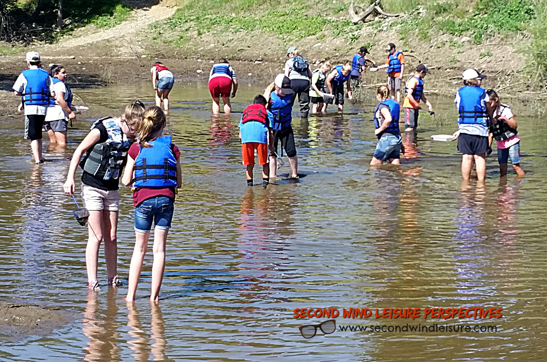 Middle school kids avert danger by wearing life jackets even in knee-deep water.