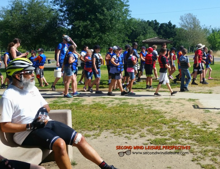 Middle School kids sporting their life jackets walk toward the river.