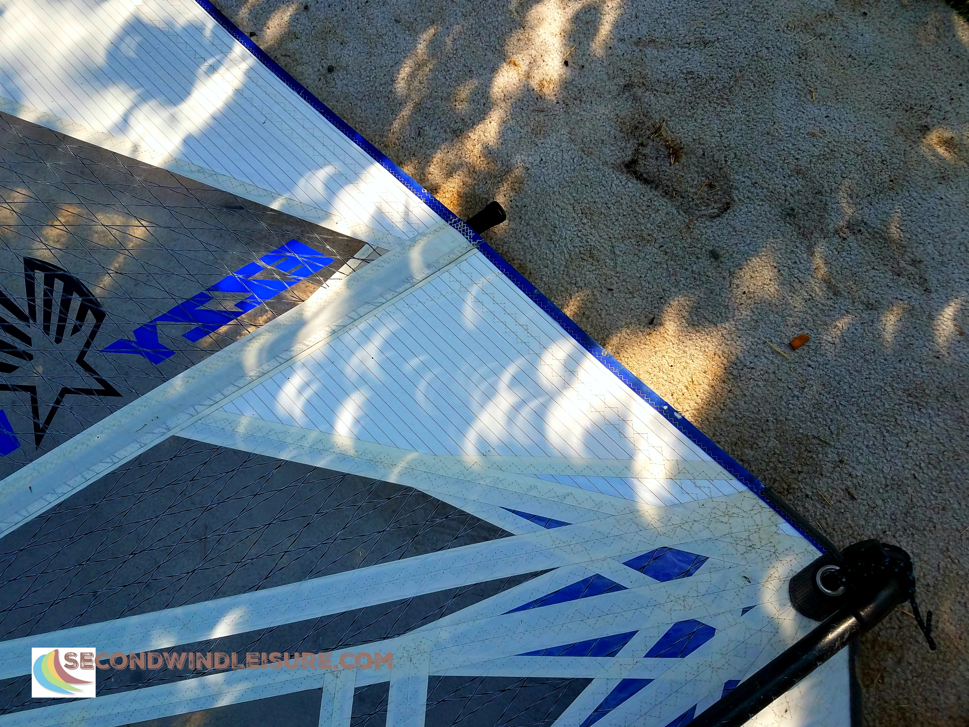 Partial solar eclipse leaves wondrous crescent shadows on a windsurf sail