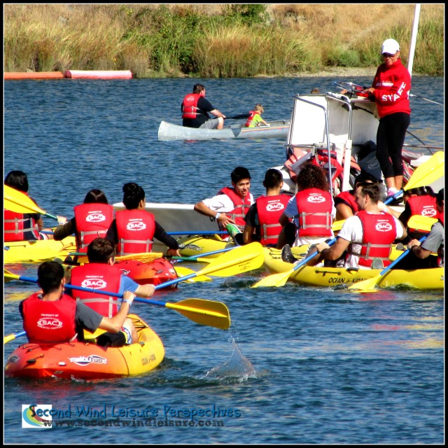 Students engage in dual kayaking for a leisure class.