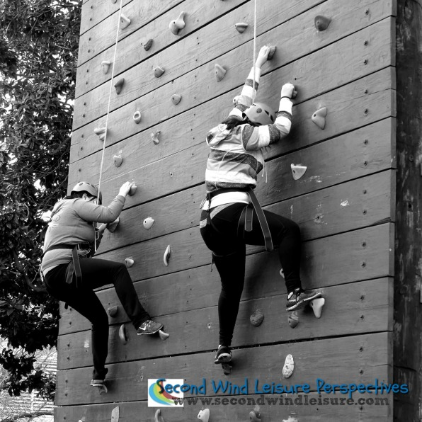 "Students carefully ""walk"" their feet on the climbing wall."