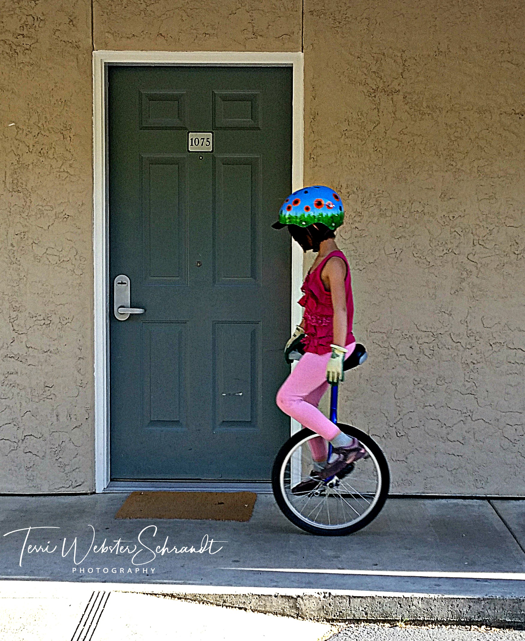 Girl on unicyle rolls by motel door
