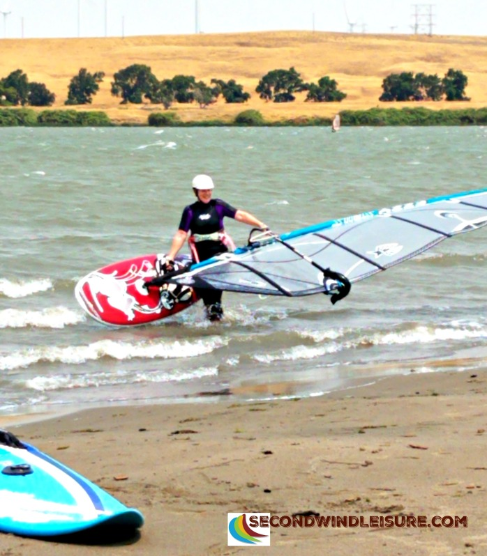 Smiling Windsurfer bringing in her windsurf gear