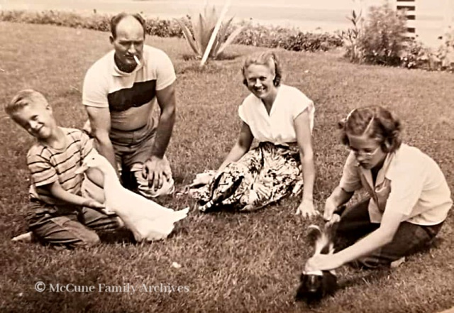 Family enjoying pet duck and skunk